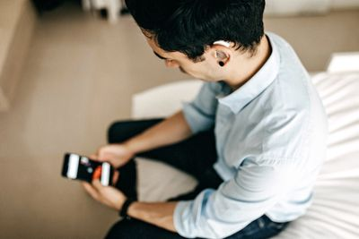 View looking down from above on someone using a smartphone and wearing a hearing aid.