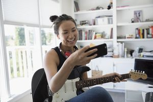 Smiling teenage girl playing electric guitar and texting with cell phone