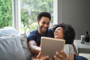 Couple having fun using digital tablet