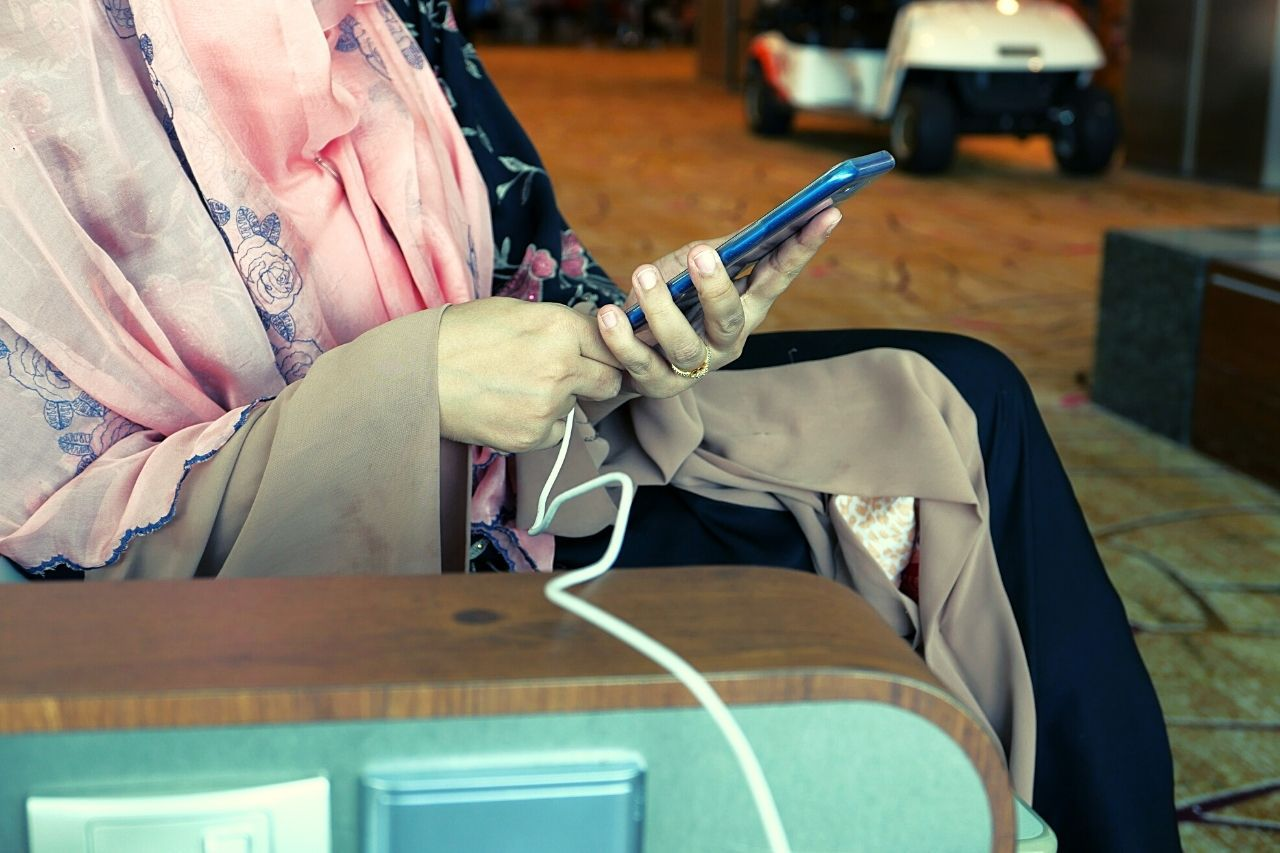 Traveler charging phone in airport.