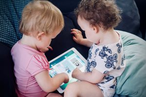 two toddlers sitting on a sofa and using an iPad