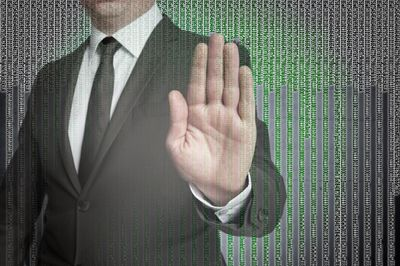 Businessman making stop symbol with his hand in front of a computer matrix background
