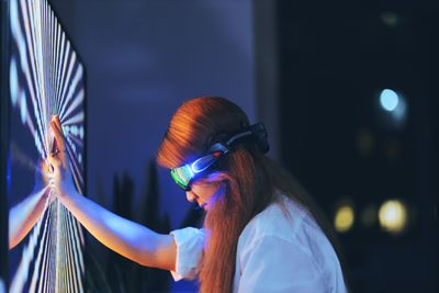 A gamer wearing augemented reality glasses, touching a TV screen with her head bowed.
