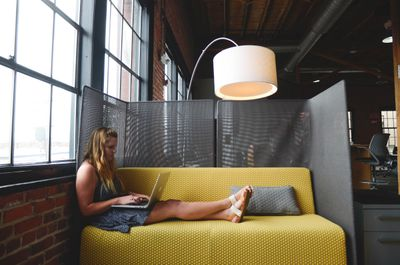 Person using laptop on yellow sofa in business setting