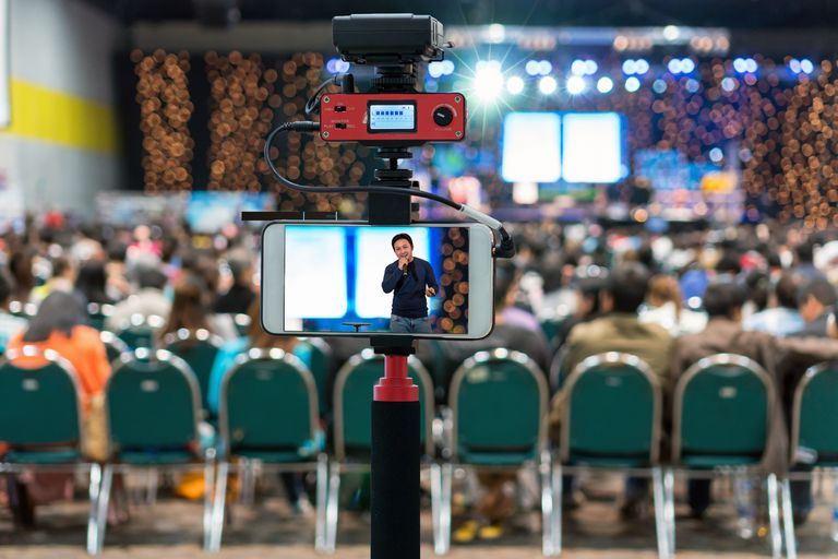 Camera for photographer or Video and Live Streaming concept,Closeup smart mobile phone taking Live of asian Businessman giving the knowledge on the tage over Audience in the conference hall