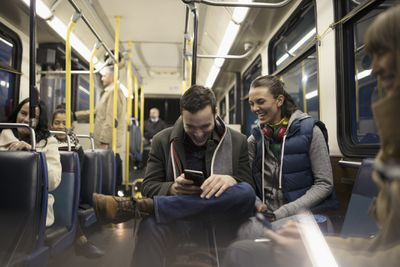 Smiling commuters texting with smartphone on bus