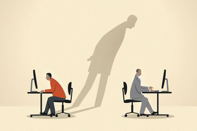 Two people working on computers with shadow looking at one of the computers