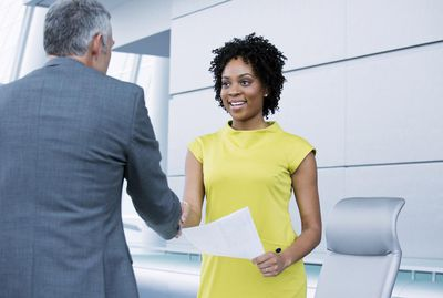 Older man in grey suit shaking hand of woman in yellow business dress