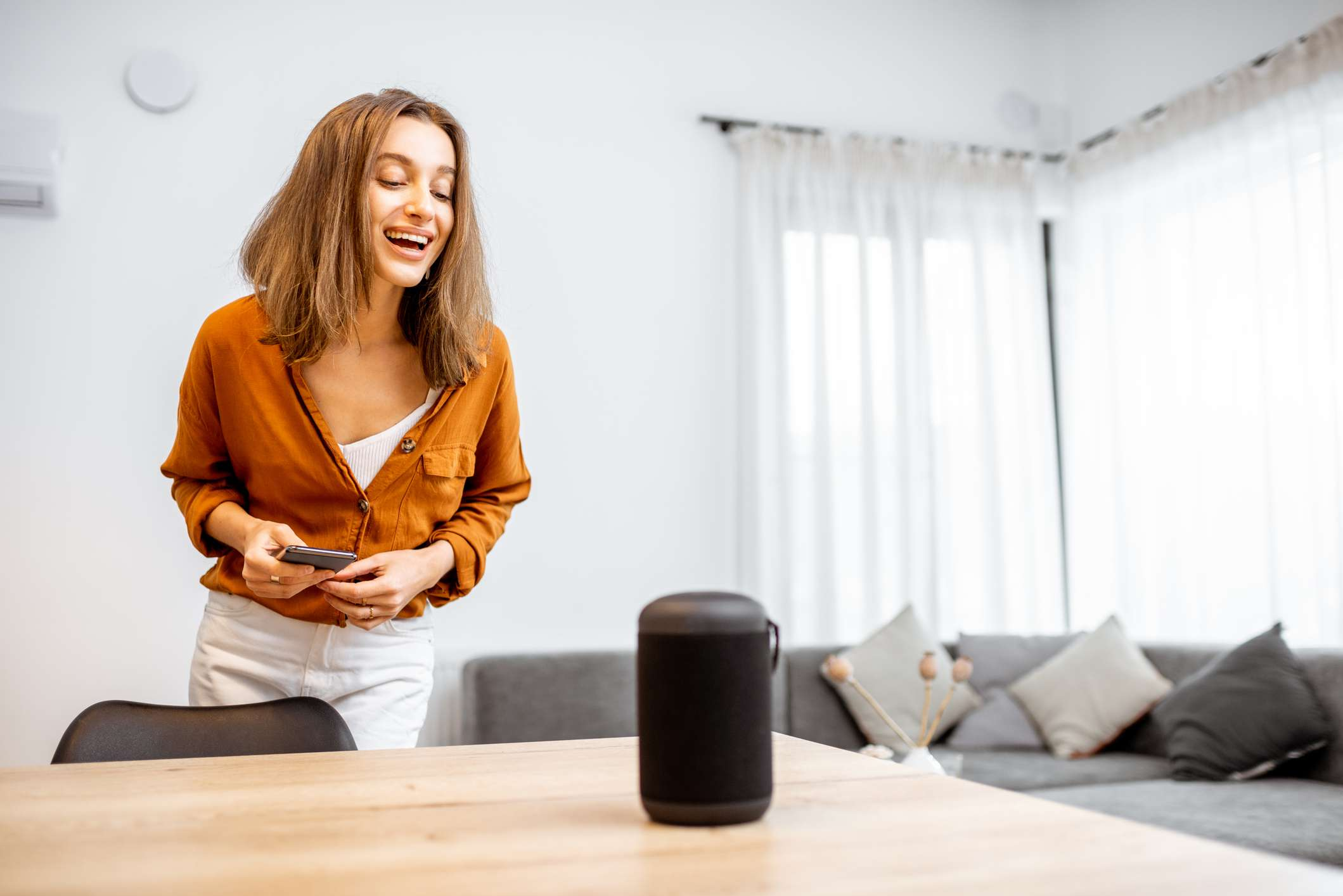 Someone talking to a smart home device in their living space.