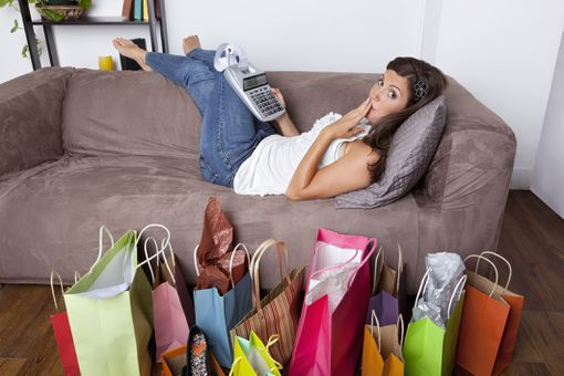 Surprised young woman lying on couch with adding machine and shopping bags