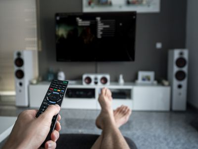 A man lying in front of a TV with his feet outstretched pointing a remote control at the TV screen.