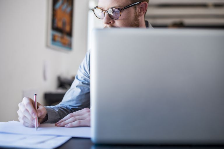 Businessman writing notes at laptop desk