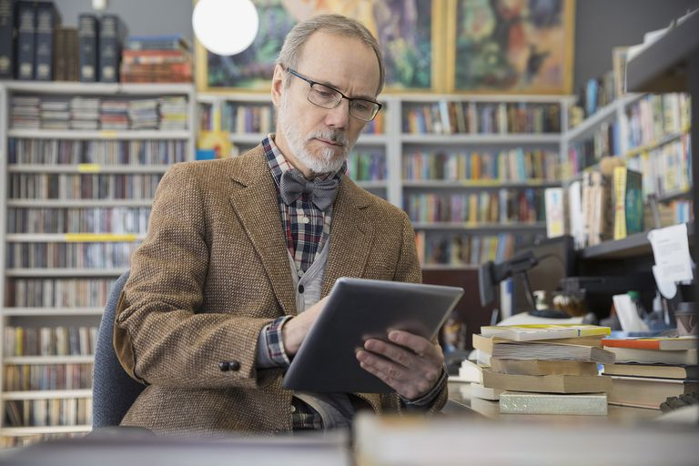 Man in office surrounded by books using iPad