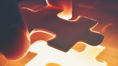 Closeup of a person placing a piece of a jigsaw puzzle down.