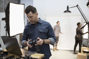 Photographer in studio using laptop