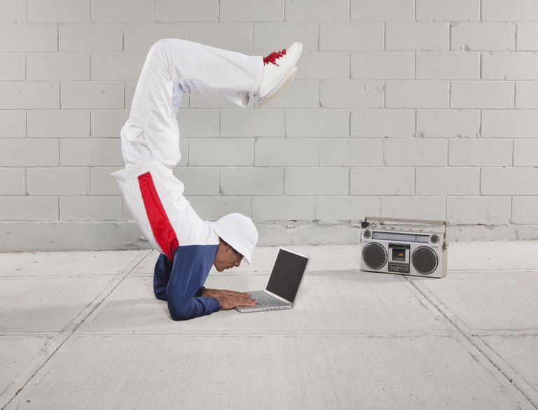 Man breakdancing while using laptop next to boombox
