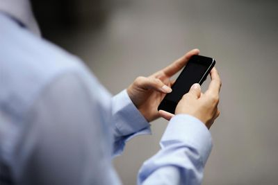 Business man's hands typing on a smart phone