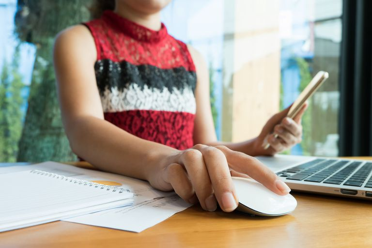 Midsection Of Woman Using Laptop While Holding Book At Table