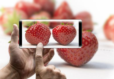 Photo of a smartphone taking a photo of strawberries