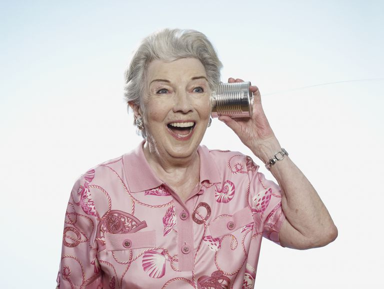 Older woman with tin can and string to her ear