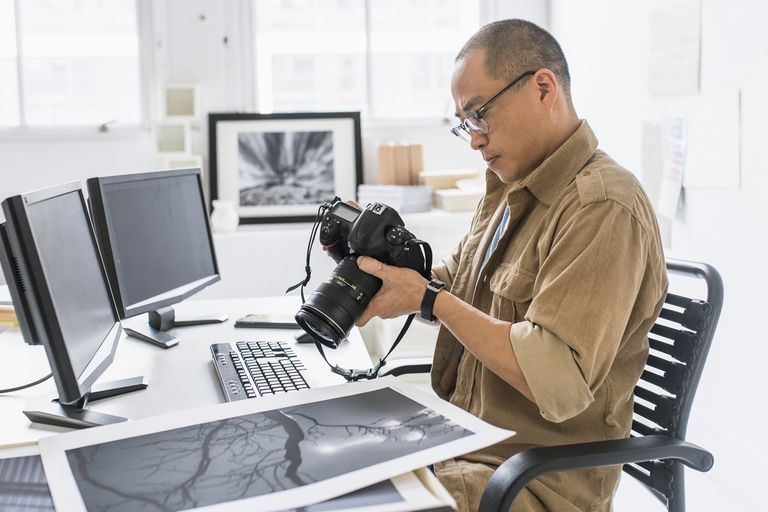 A photographer looks at his photos on camera and printed