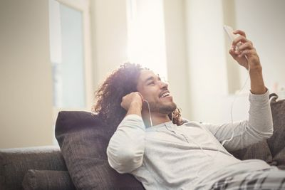 Man relaxing on couch using facetime on an iPod with headphones in