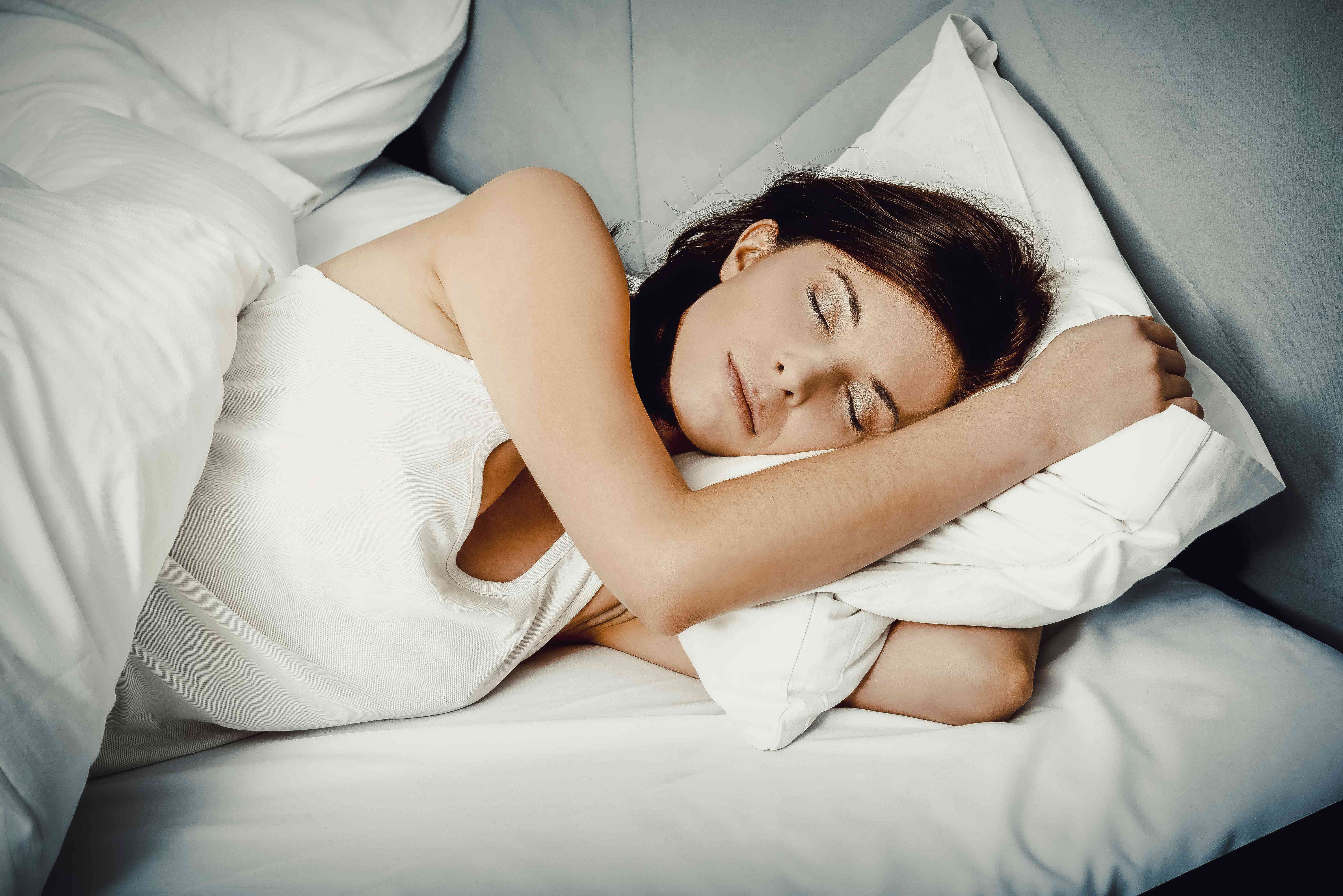 A woman is sleeping peacefully in a bed.