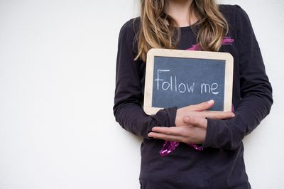 "Girl holding sign with the words ""Follow me"""