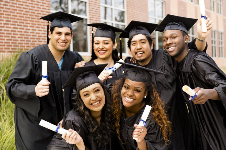 A group of multi-ethnic graduates smiling and holding diplomas