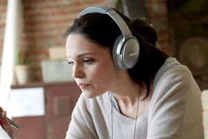 A woman wearing Bose noise-cancelling headphones.
