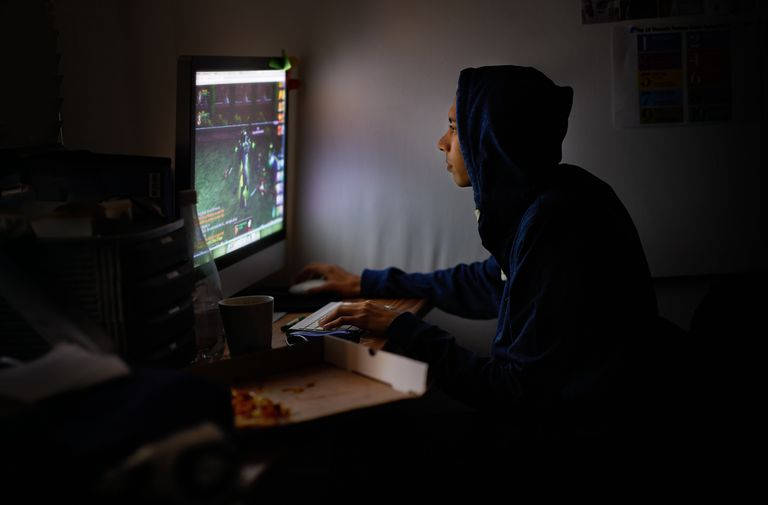 Teen playing computer video game in dark room