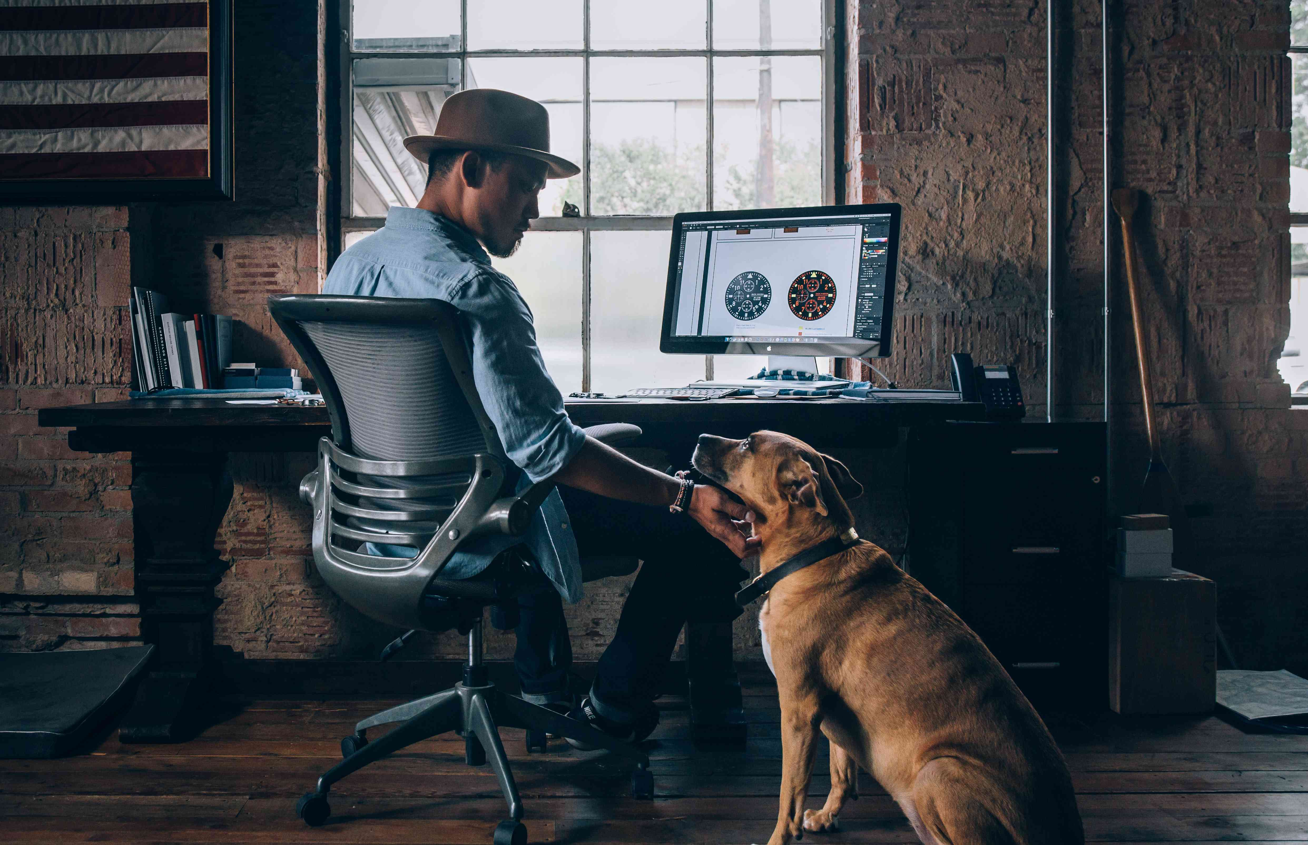Someone sitting in a desk chair in a home office, petting a dog.
