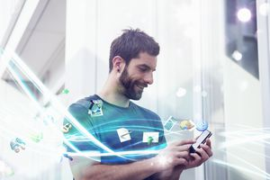 Mid adult man with apps and lights coming from smartphone