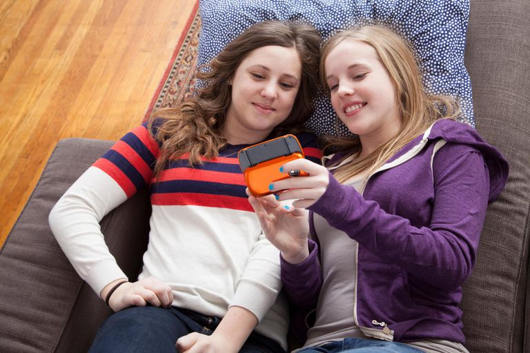 Girls lying on sofa playing handheld video game