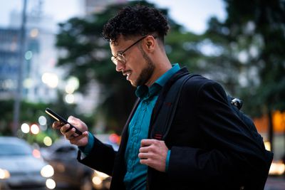 Profile image of a young man wearing glasses and carrying a backpack looking at his phone.