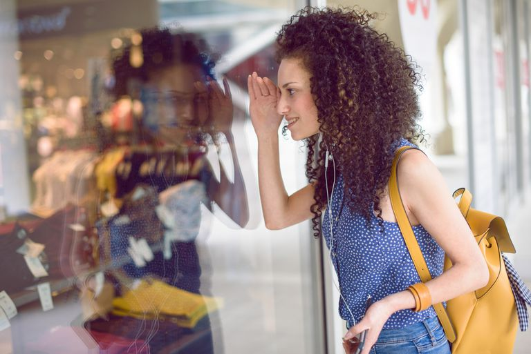 A woman windows shopping with a wishful look on her face.