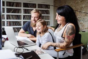 Hipster family gathered around a laptop, laughing