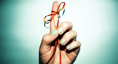 Photo of a woman's hand with a string tied around her finger, representing a reminder for something