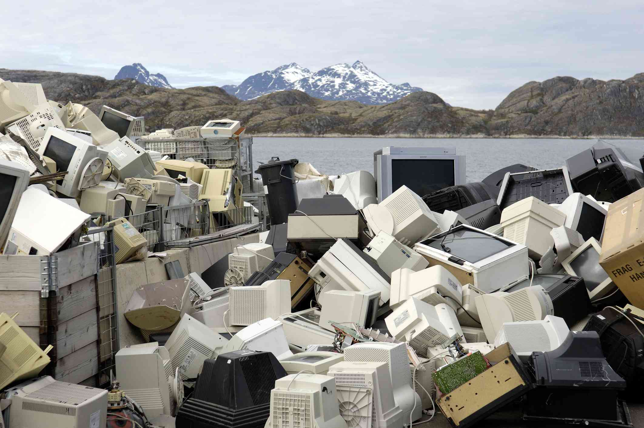 Piles of e-waste (old computer and electronics) in a landfill with a lake and mountains in the background.