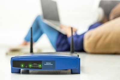 Close-Up Of Router Against Woman Using Laptop At Home