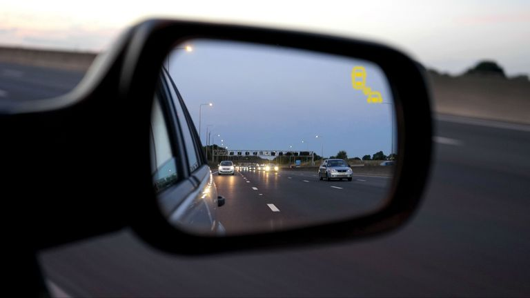 A blind spot detection warning indicator on a car mirror.