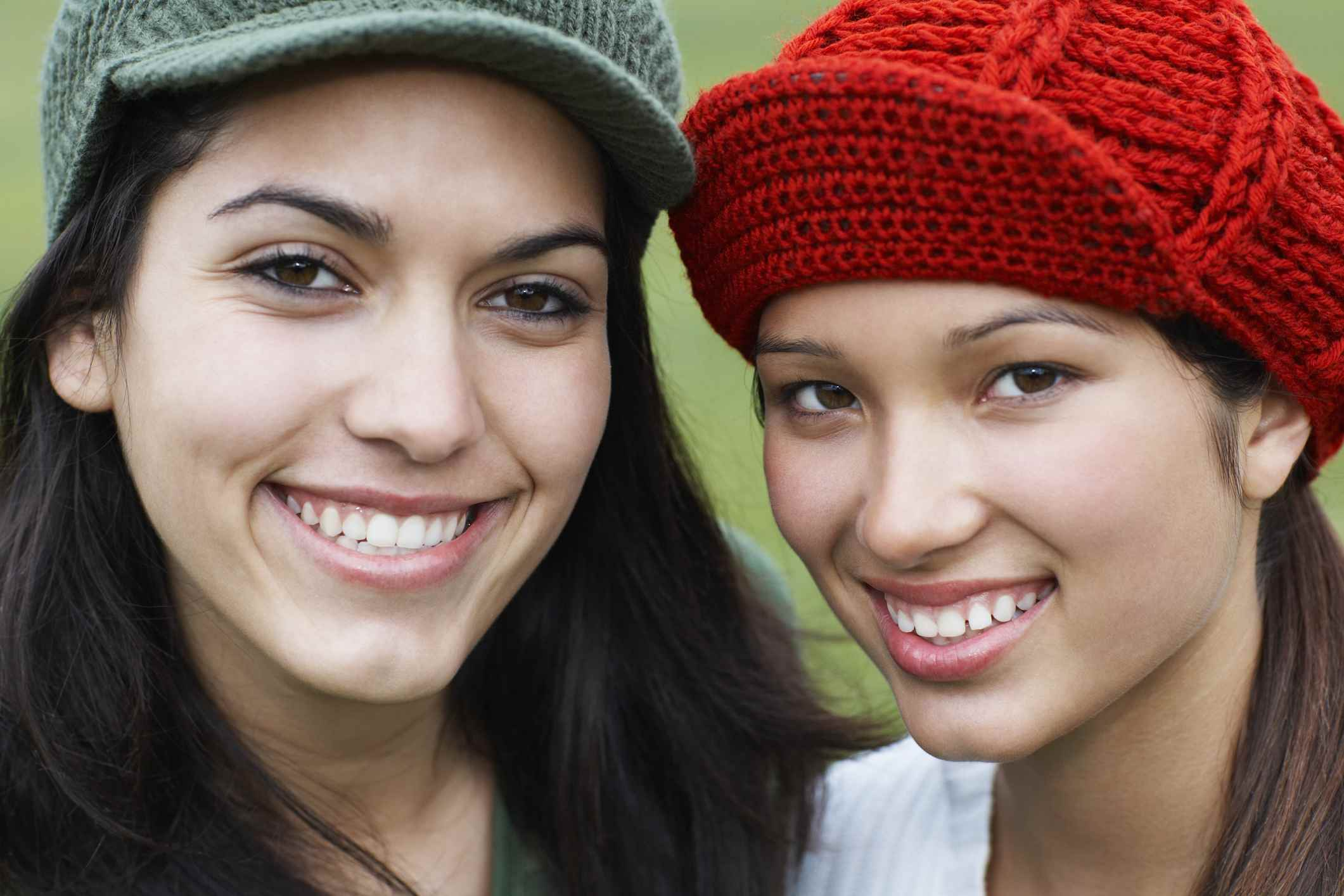 Two women in knit caps smiling together