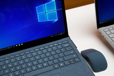 A close-up stock photo of two Microsoft Surface laptops on a white table. The main laptop which is blue, has a blue wireless mouse sitting next to it.