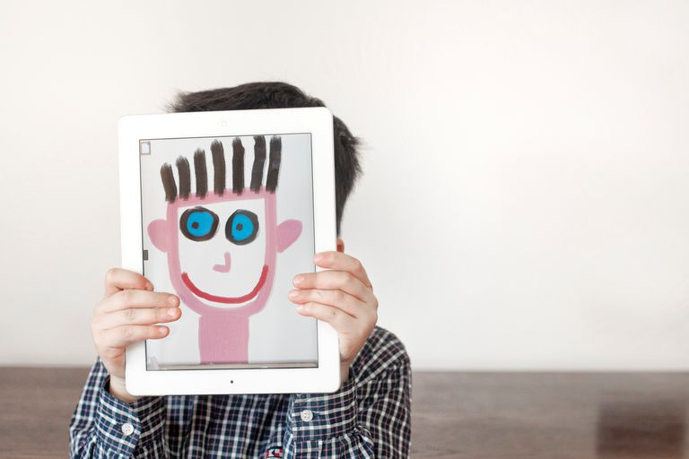 young boy holding tablet in front of his face with image of painted face.