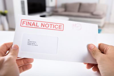 A person holds a final notice bill envelope.