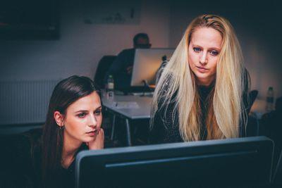 Two women looking at desktop computer monitor.