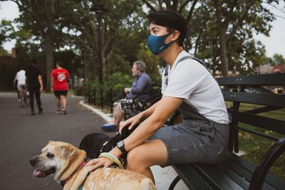 Masked person sitting on a park bench with a dog.