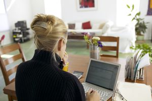 Remote worker checking email on laptop in a home setting