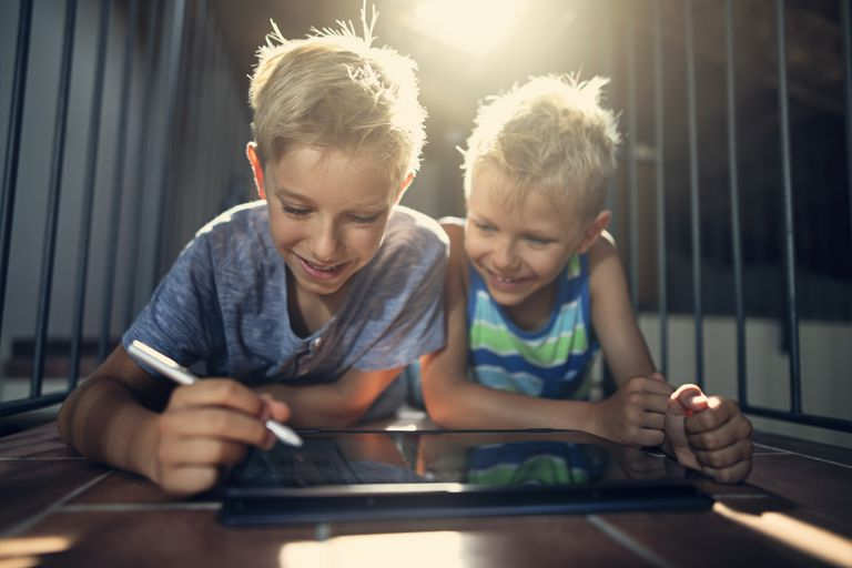 Two boys use a drawing stylus after enabling the touchscreen on a Windows 10 laptop.