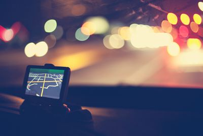 In-car GPS device on dashboard, driving at night